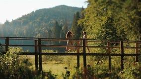 Belle giovani coppie felici in vestiti ucraini tradizionali che camminano e che si divertono sul ponte di legno in montagne stock footage
