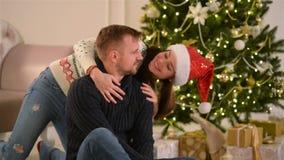 Belle giovani coppie nell'amore che indossa Santa Hats, trovantesi sul pavimento accanto ad un camino e ad un Nizza decorato video d archivio