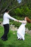 Belle giovani coppie nell'amore su una radura verde Fotografie Stock