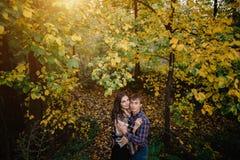 Belle giovani coppie nella foresta accanto agli alberi con le foglie ingiallite immagine stock