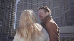 Belle giovani coppie nello stare di conversazione di amore contro il contesto di grande edificio residenziale moderno archivi video