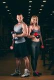 Belle giovani coppie sexy sportive che mostrano muscolo e allenamento nella testa di legno della palestra Immagine Stock Libera da Diritti