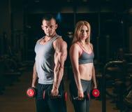 Belle giovani coppie sexy sportive che mostrano muscolo e allenamento nella testa di legno della palestra Immagini Stock