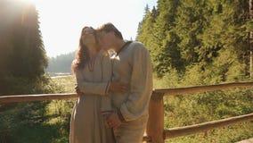 Belle giovani coppie in vestiti ucraini tradizionali che abbracciano morbidamente sul ponte di legno in montagne maestoso stock footage
