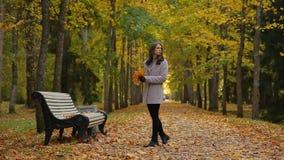 Belle giovani donne che camminano intorno e che si siedono sul banco nel parco in autunno, aspettante qualcuno archivi video