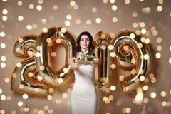 Belle giovani donne che celebrano gioco tenendo i palloni Nuovo anno, natale, natale fotografie stock libere da diritti