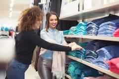 Belle giovani donne che comperano in un boutique per i vestiti Giovani belle donne al mercato settimanale del panno Fotografie Stock
