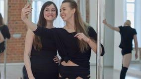 Belle giovani donne che prendono un selfie durante una pausa su una classe di forma fisica del palo Fotografia Stock