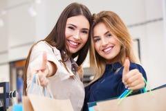 Belle giovani donne con i sacchetti della spesa che mostrano i pollici su Immagini Stock
