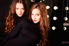 Belle giovani donne dei gemelli nei corpi neri sopra fondo scuro in uno spogliatoio Fotografia Stock Libera da Diritti