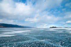 Belle glace transparente avec des fissures du lac Baïkal en mars photos stock