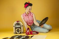 Belle goupille de portrait écoutant la musique sur un vieux juke-box r Photographie stock libre de droits