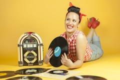Belle goupille de portrait écoutant la musique sur un vieux juke-box r Photos stock