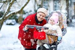 Belle grand-mère marchant avec le bébé dans le landau pendant les chutes de neige en hiver Photographie stock