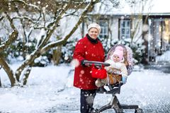 Belle grand-mère marchant avec le bébé dans le landau pendant les chutes de neige en hiver Images stock