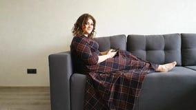 Belle grosse fille sur le sofa avec la relaxation de téléphone banque de vidéos
