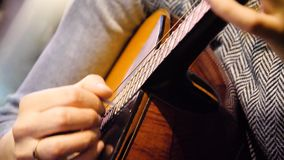 Belle guitare acoustique de plan rapproché joué par la femme s'asseyant, concept de musicien Femme jouant le plan rapproché de gu photographie stock libre de droits