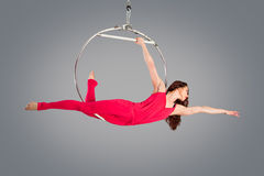 Belle gymnaste de plastique de fille sur l'anneau acrobatique de cirque dans le costume carné Image stock