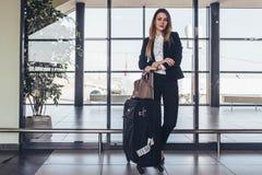 Belle hôtesse de l'air se tenant dans son uniforme avec ses valises prêtes pour un vol photos libres de droits
