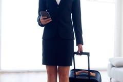 Belle hôtesse dans l'aéroport avec le téléphone portable Photo stock