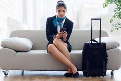 Belle hôtesse dans l'aéroport avec le téléphone portable Photo libre de droits