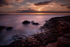 Belle image de coucher du soleil au sujet d'horizon de mer, et formations de roche volcanique uniques à la chaussée de Giants, No images stock
