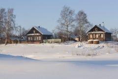 Belle image de l'hiver landscape Deux belles maisons en bois au milieu de la neige Sont près de là des tas de bois Beau photos libres de droits