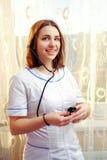 Belle infirmière de jeunes à la fenêtre image libre de droits