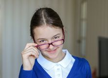 Belle jeune écolière de sourire dans l'uniforme regardant au-dessus du dessus des verres l'appareil-photo, plan rapproché De nouv photos stock
