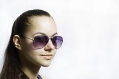 Belle jeune adolescente dans des lunettes de soleil au-dessus du fond blanc Images libres de droits