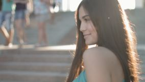 Belle jeune brune dans les raies du coucher de soleil saluant quelqu'un sur la rue clips vidéos