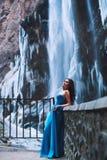 Belle jeune brune dans une robe bleue sur un fond d'un massif de montagne et d'un glacier Image libre de droits