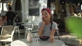 Belle jeune brune en verres portant le faire-chiffon rouge et la pièce en t grise se reposant dans restourant extérieur et parlan clips vidéos
