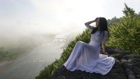 Belle jeune dame dans une robe de mariage blanche seul se reposant près de la rivière avec ses yeux fermés Images stock