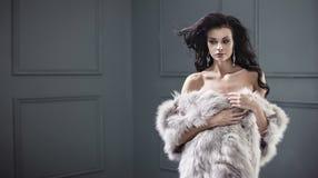 Belle jeune dame de brune utilisant le manteau de fourrure élégant photographie stock libre de droits