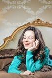 Belle jeune dame parlant au téléphone portable se trouvant sur le sourire heureux de lit Verticale de plan rapproché Photos stock