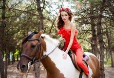 Belle jeune dame portant la robe rouge montant un cheval au jour d'été ensoleillé Brune avec de longs cheveux bouclés avec des fl Photographie stock libre de droits