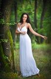 Belle jeune dame portant une longue robe blanche élégante appréciant les faisceaux de la lumière céleste sur son visage en bois e Photo libre de droits