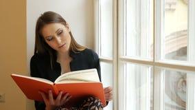 Belle jeune dame rêveuse posant sur le rebord de fenêtre et lisant un livre banque de vidéos
