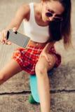 Belle jeune dame sexy dans la mini jupe érotique avec une planche à roulettes Photo libre de droits