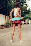 Belle jeune dame sexy dans la mini jupe érotique avec une planche à roulettes Images stock