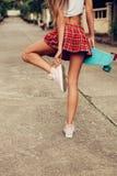 Belle jeune dame sexy dans la mini jupe érotique avec une planche à roulettes Image libre de droits