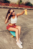 Belle jeune dame sexy dans la mini jupe érotique avec une planche à roulettes Images libres de droits