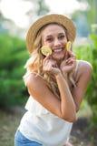 Belle jeune dame sur un fond de parc Une femelle de sourire dans un chapeau, tenant des citrons Régimes exotiques Style de vie sa photo stock