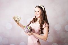 Belle jeune dame tenant les billets de banque des USA et la tirelire Photo stock