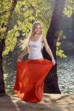 Belle jeune danse blonde de femme sous les arbres sur la rive Images stock