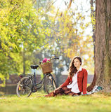 Belle jeune femelle avec la bicyclette se reposant en parc et regard Image libre de droits
