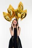 Belle jeune femelle joyeuse recherchant sur les ballons en forme d'étoile Images libres de droits