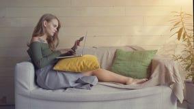 Belle jeune femme à l'aide d'un ordinateur portable, tenant une carte de crédit et souriant tout en faisant l'achat en ligne à la banque de vidéos