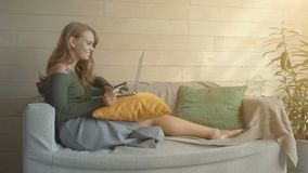 Belle jeune femme à l'aide d'un ordinateur portable, tenant une carte de crédit et souriant tout en faisant l'achat en ligne à la clips vidéos